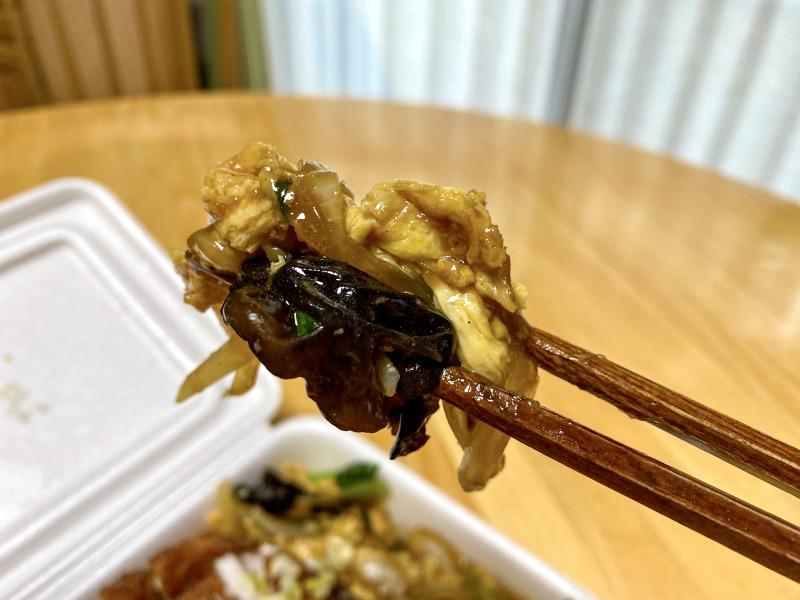 大阪王将浜田山店のスーパーノリ弁当の玉子と木耳の炒めものを食べるところ